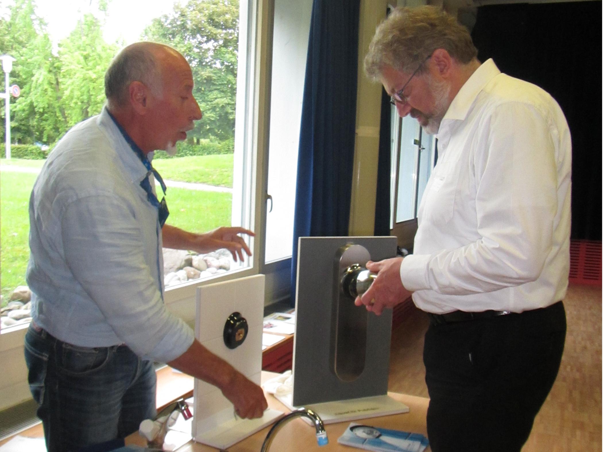 Paul Eggimann vom Bundesamt für Bauten und Logistik lässt sich von Paul Curty die wassersparenden Duschbrausen erklären.